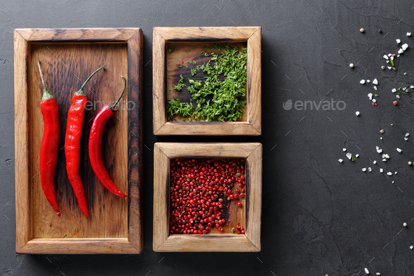Diverse spices and chilli in wooden boxes on dark background, top view, copy space - Stock Photo - Images