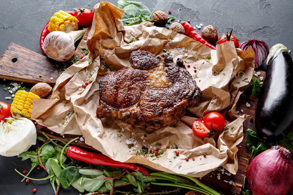 Rib eye steak on cooking paper, parchment with vegetables border on dark background - Stock Photo - Images