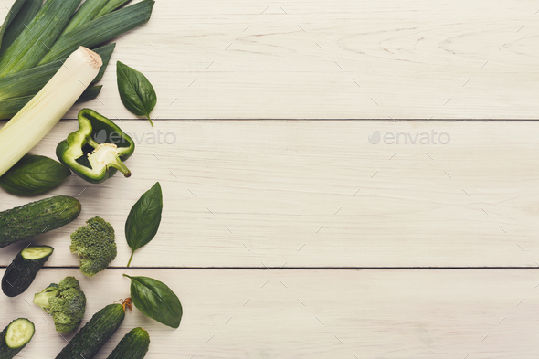 Border of various green vegetables on white wood - Stock Photo - Images