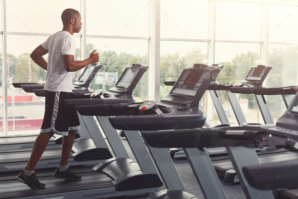 Young man in gym run on treadmill - Stock Photo - Images