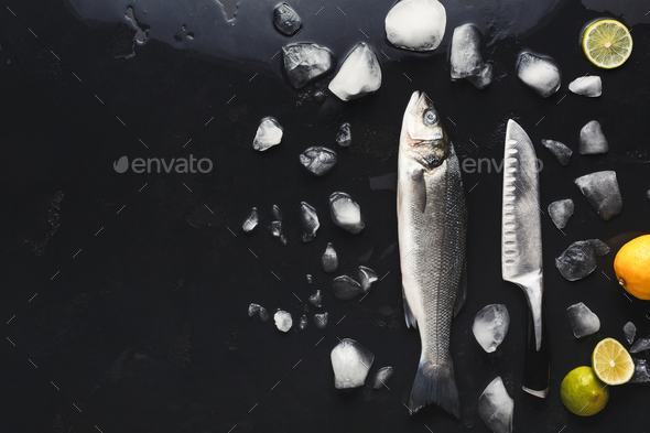 Fresh sea bass with ice at black background - Stock Photo - Images