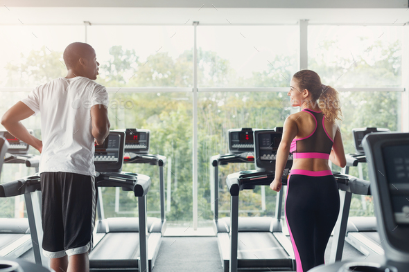 Man and woman, couple in gym on treadmills - Stock Photo - Images