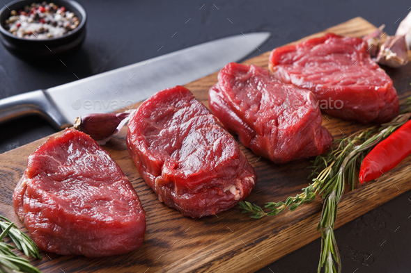 Filet mignon steaks and spices on wood at black background - Stock Photo - Images