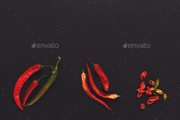 Whole and cut chili pepper on black isolated background - Stock Photo - Images