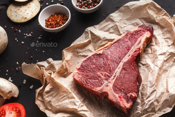 Raw t-bone steak on craft papper on dark background - Stock Photo - Images