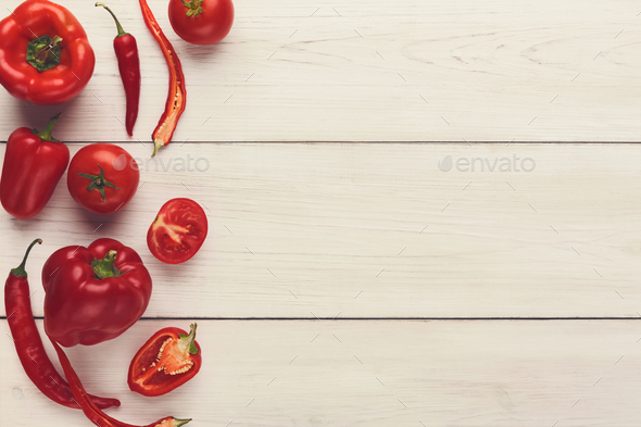 Border of various red vegetables on white wood - Stock Photo - Images