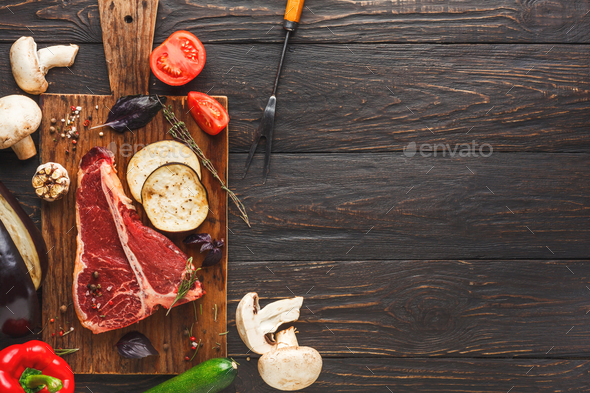 Raw t-bone steak on wooden board - Stock Photo - Images