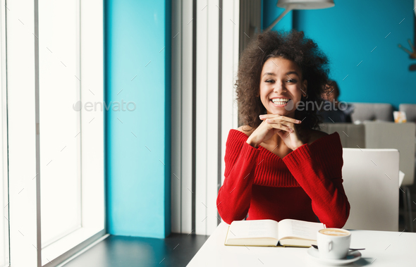 Happy black girl at cafe reading a book - Stock Photo - Images
