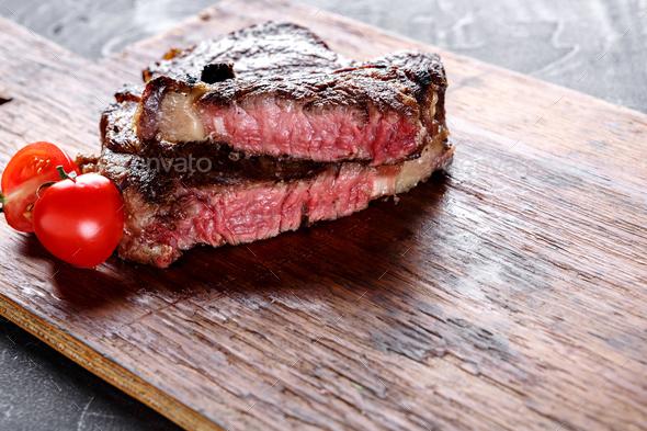 Rare rib eye steak on wooden board, closeup - Stock Photo - Images