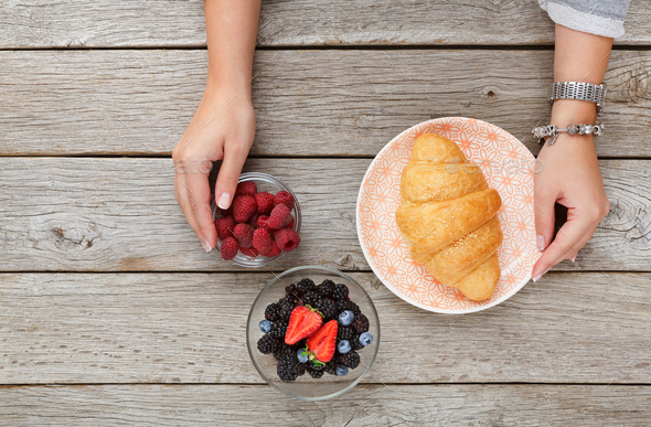 Female hands serving breakfast table with croissant and berries - Stock Photo - Images