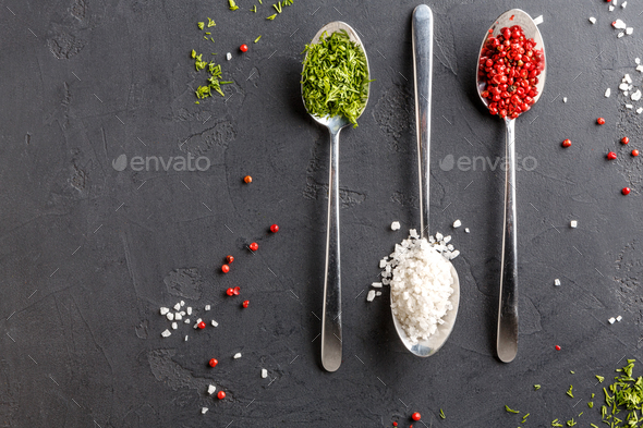 Diverse spices in spoons on dark background, top view, copy space - Stock Photo - Images