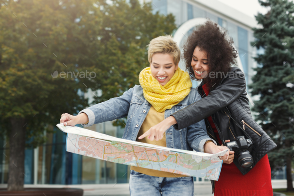 Two girl friends outdoors with paper city map - Stock Photo - Images