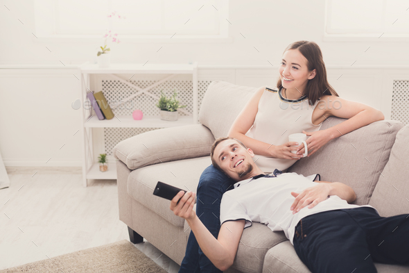 Smiling young couple watching TV at home - Stock Photo - Images