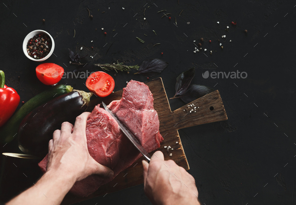 Chef cutting filet mignon on wooden board at restaurant kitchen - Stock Photo - Images
