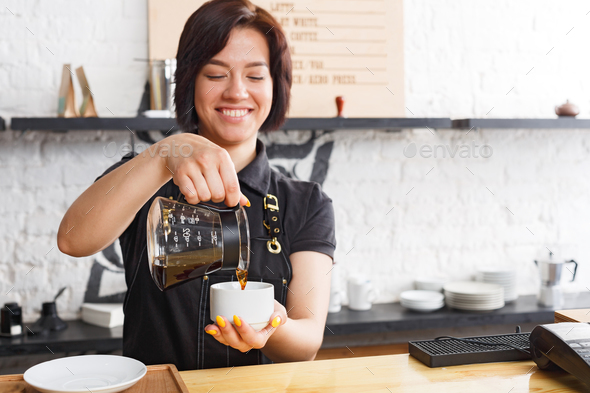 Portrait of young barista at coffee shop counter - Stock Photo - Images