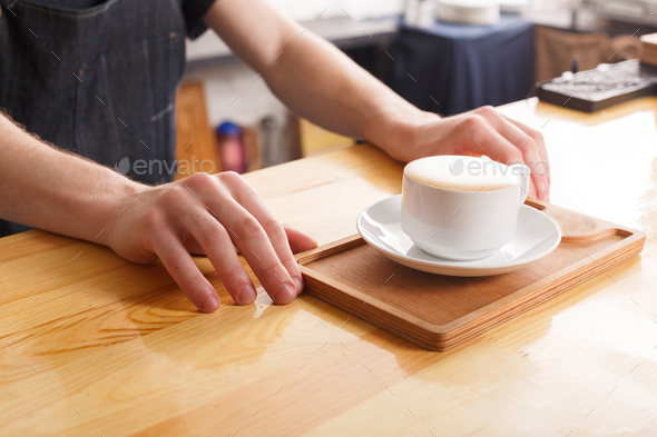 Barman serving coffee cup on wooden bar counter - Stock Photo - Images