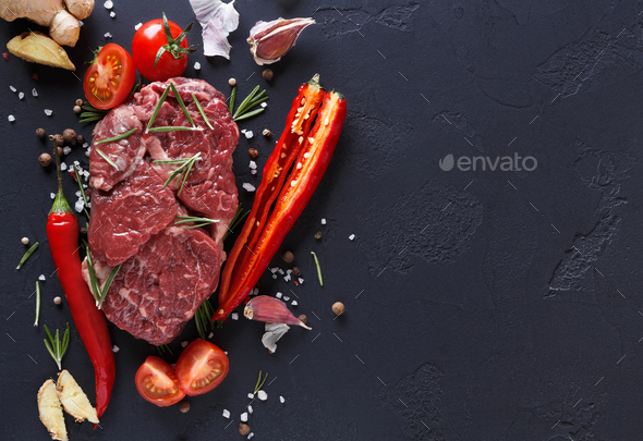 Rib eye steak, spices and vegetables at black background - Stock Photo - Images