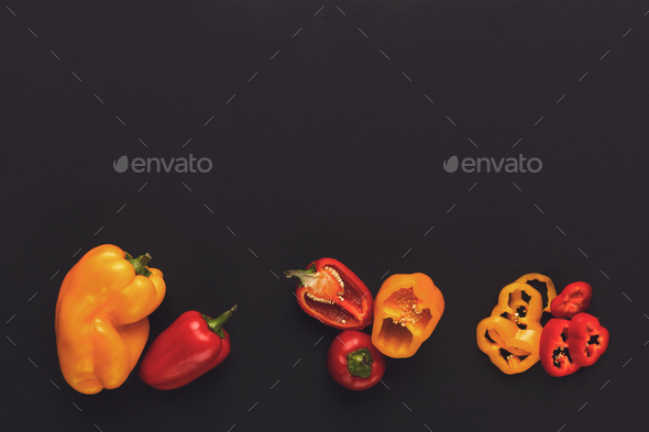 Whole and cut bell pepper on black isolated background - Stock Photo - Images