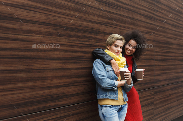 Happy girls with take away coffee outdoors - Stock Photo - Images