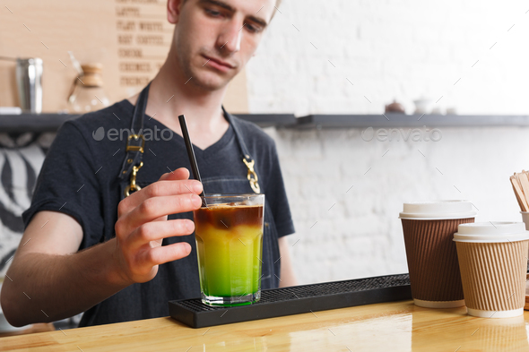 Concentrated bartender making coffee cocktail at cafe counter - Stock Photo - Images