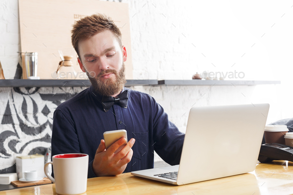 Pensive barman working on laptop at bar counter - Stock Photo - Images