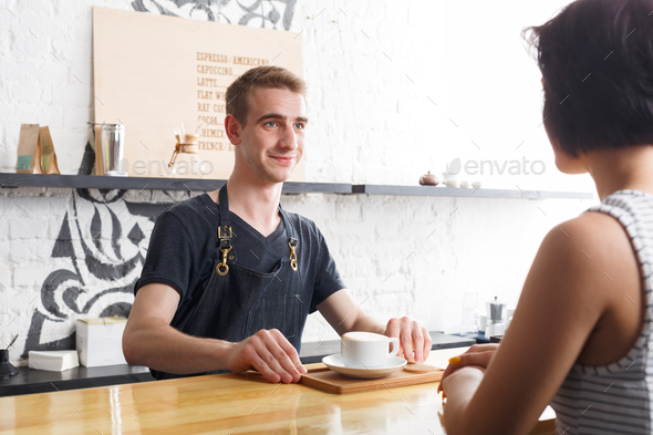 Barman chatting with the guest and serving coffee - Stock Photo - Images