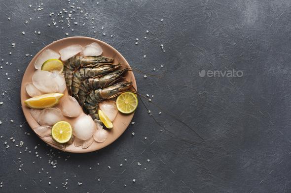 Raw shrimps with lemon on black background - Stock Photo - Images