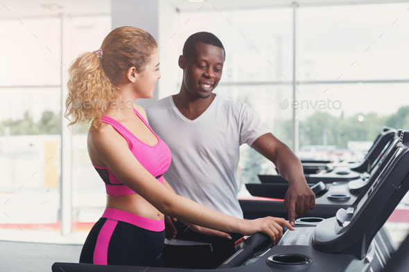 Fitness instructor helps young woman on treadmill - Stock Photo - Images