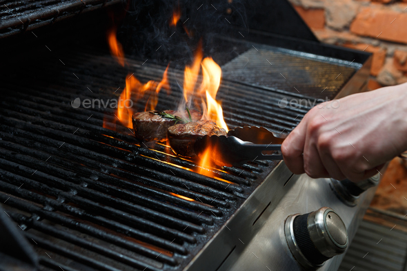 Man cooking meat steaks on professional grill outdoors - Stock Photo - Images