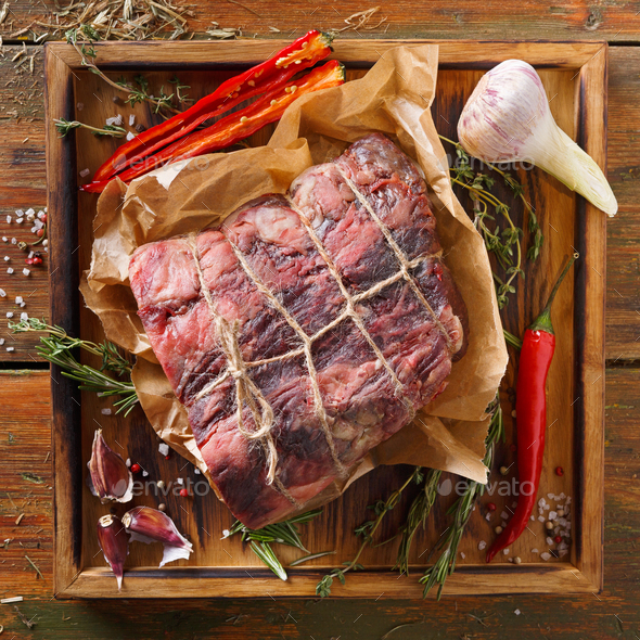 Raw aged prime black angus beef in craft papper on rustic wood - Stock Photo - Images