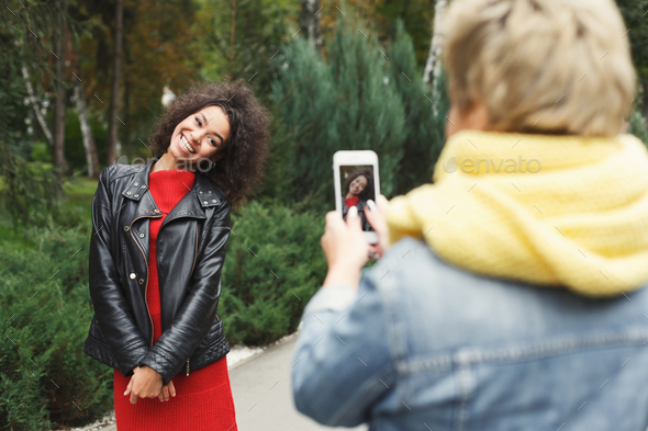 Happy girls with smartphone outdoors in the park - Stock Photo - Images