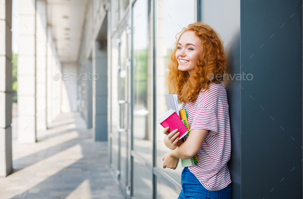 Young smiling redhead student girl with cup of coffee and books - Stock Photo - Images