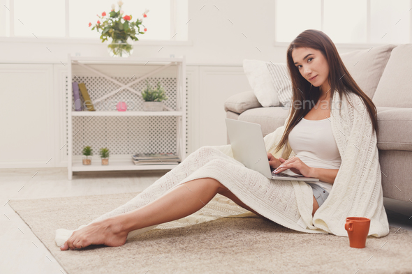 Cozy home. Girl in blanket with laptop - Stock Photo - Images