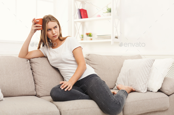 Thoughtful woman at home with coffee - Stock Photo - Images