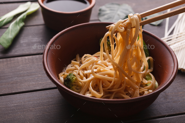 Bowl of rice noodles with soy souce on wood - Stock Photo - Images