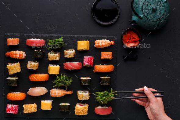 Set of sushi maki and rolls on black background - Stock Photo - Images