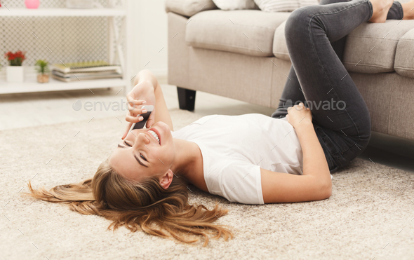 Smiling girl at home talking on mobile phone - Stock Photo - Images