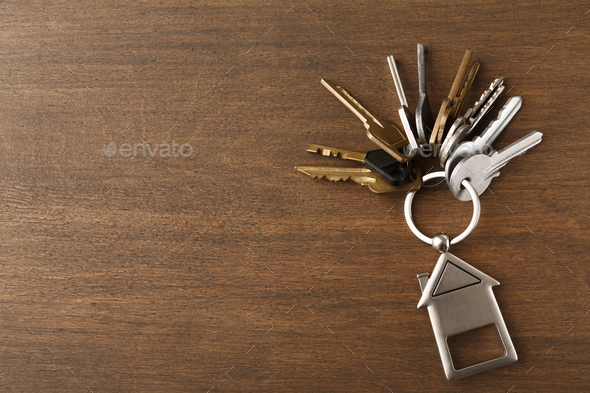 Bunch of keys with house shaped keychain on white wood - Stock Photo - Images