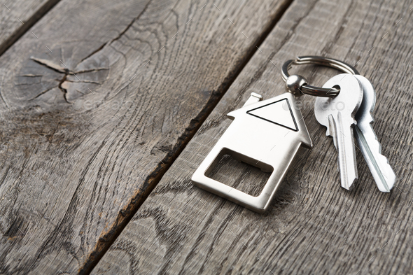 Bunch of keys with house shaped keychain on rustic wood - Stock Photo - Images