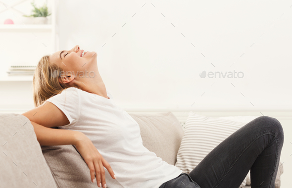 Young blonde woman sitting on beige couch - Stock Photo - Images