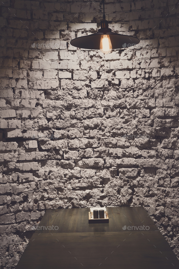 Brick grunge wall and ceiling lamp above table - Stock Photo - Images