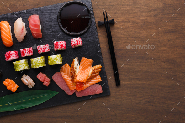 Set of sushi maki and rolls on black rustic wood, top view - Stock Photo - Images
