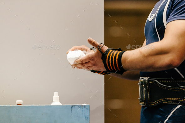 man powerlifter puts hands in chalk - Stock Photo - Images
