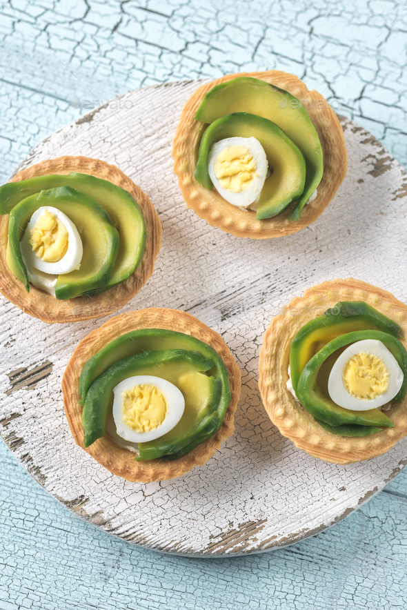 Tartlets with cream cheese, avocado and quail eggs - Stock Photo - Images