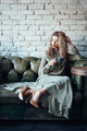 young beautiful woman sitting on a couch - PhotoDune Item for Sale