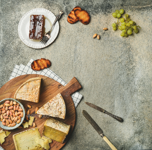 Flat-lay of platter with cheese assortment and snacks, copy space - Stock Photo - Images