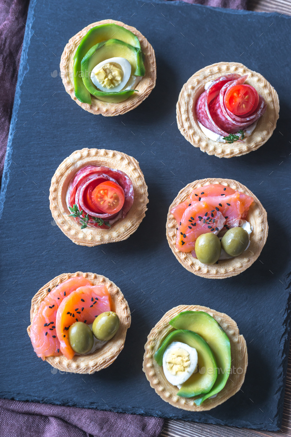 Tartlets with different fillings on the stone board - Stock Photo - Images