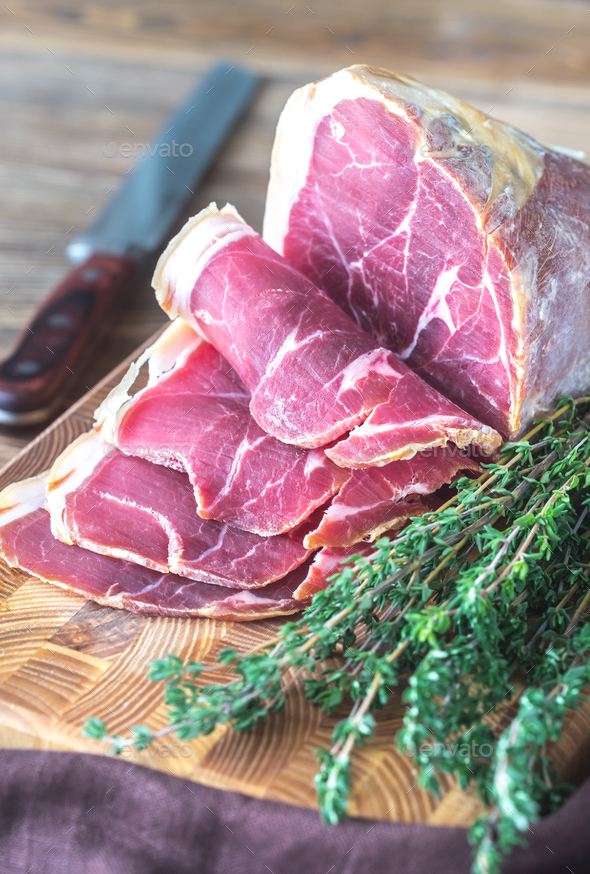 Prosciutto with fresh thyme on the wooden board - Stock Photo - Images