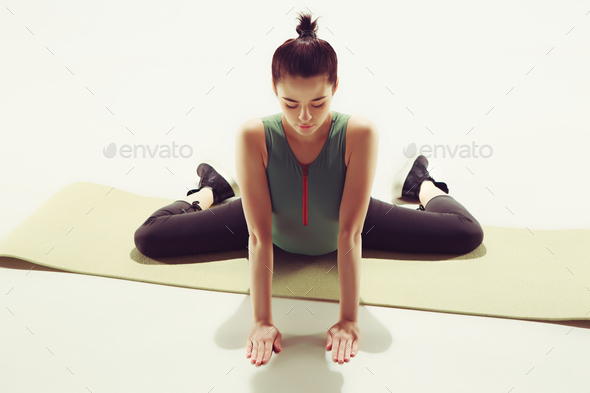 Beautiful slim brunette doing some stretching exercises in a gym - Stock Photo - Images