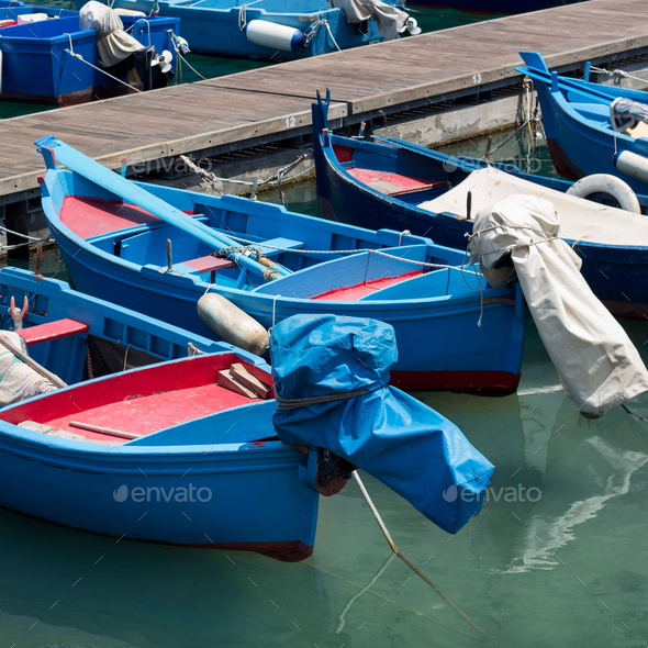 Blue and red fishing boats in harbour, south Italy - Stock Photo - Images